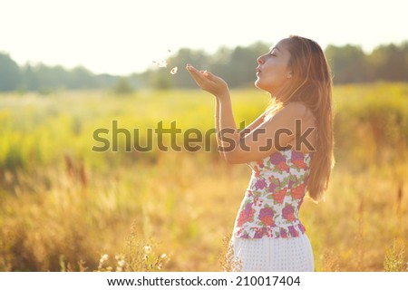 Happy european young woman in summer blooming field blows out fluff from hands under evening sun - stock photo