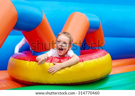 happy excited boy having fun on inflatable attraction playground - stock photo