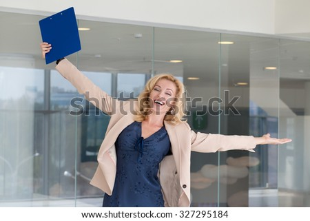 Happy excited business woman celebrating with arms up - stock photo