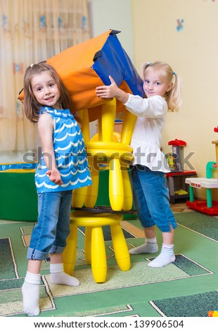 Happy excited children building tower from toy chairs - stock photo