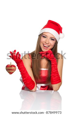 Happy excited christmas santa girl smile looking at camera sitting at the table hold toy heart, isolated on white background - stock photo