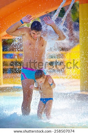 happy excited family under water stream in aqua park - stock photo