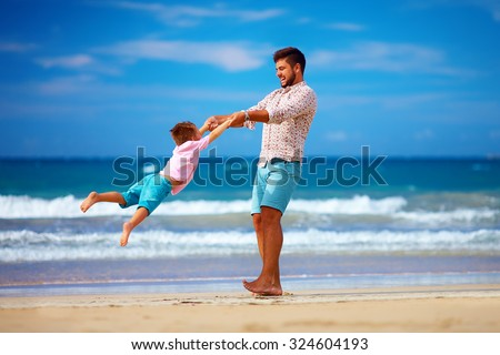 happy excited father and son having fun on summer beach, enjoy life