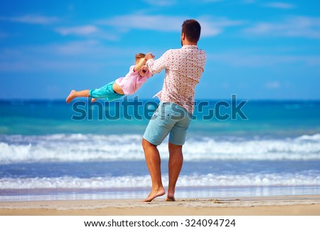 happy excited father and son playing on summer beach, enjoy life