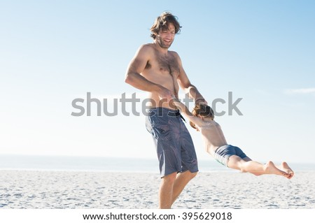 Happy excited father and son playing on white beach. Father playing with his son at seashore. Happy father holding hands child in a summer vacation.