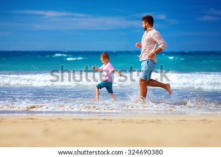 happy excited father and son running on summer beach, enjoy life - stock photo