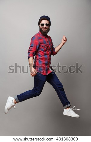 happy excited jmping young bearded man. Funny portrait on young casual male model in humorous jump on grey background. - stock photo