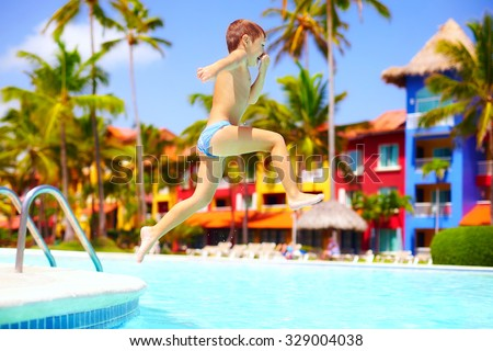 happy excited kid jumping in pool on summer vacation