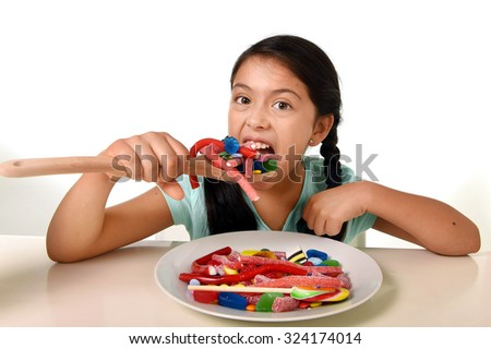 happy excited Latin female child holding spoon eating from a dish full of candy , lollipop and sugary things in unhealthy sweet nutrition and kid in sugar abuse concept - stock photo