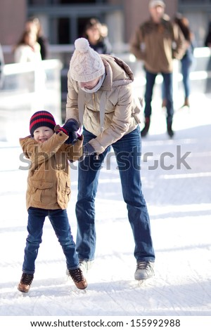 happy excited little boy and his young mother learning ice-skating - stock photo