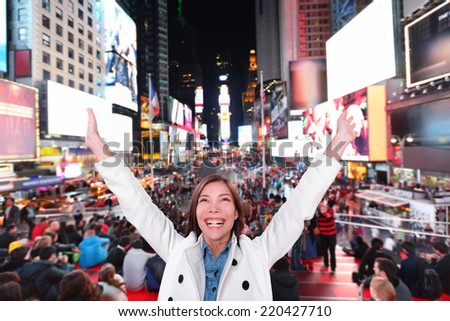 Happy excited woman in New York City, Manhattan, Times Square cheering celebrating joyful at night with arms raised. Smiling cheerful Multiethnic Asian Caucasian young urban professional in her 20s. - stock photo
