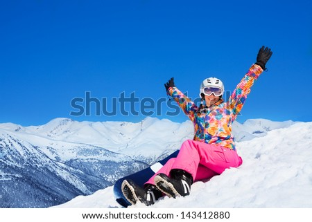 Happy excited woman in pink sit on snow holding snowboard with lifted hands