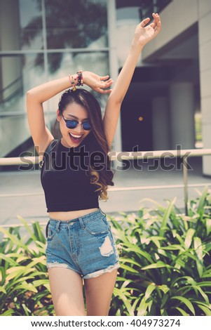 Happy excited young woman dancing outdoors - stock photo