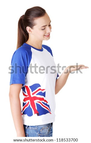 Happy , excited young woman in tshirt with british flag showing copy space, isolated on white