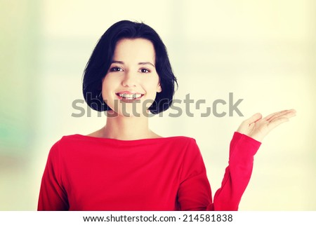 Happy , excited young woman presenting copy space on her palm, isolated on white - stock photo