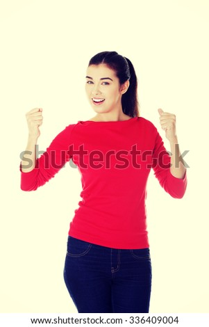 Happy ,excited young woman with fists up - stock photo