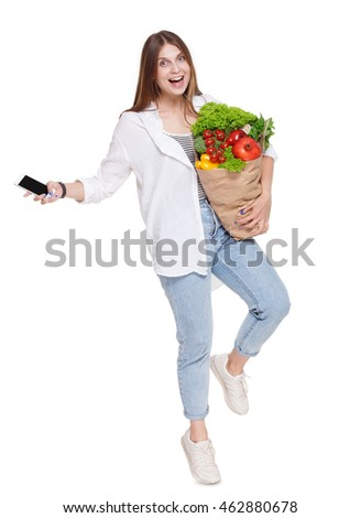 Happy excited young woman with mobile full length portrait, holding shopping bag full of groceries isolated at white background. Healthy food shopping. Paper package with vegetables, female buyer