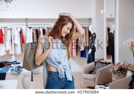 Happy excited young woman with shopping bags in clothing store - stock photo