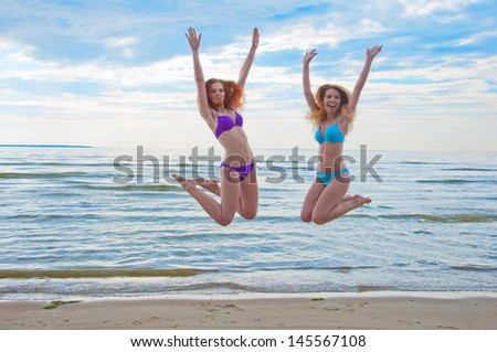 Happy excited young women in bikini jumping on beach. - stock photo