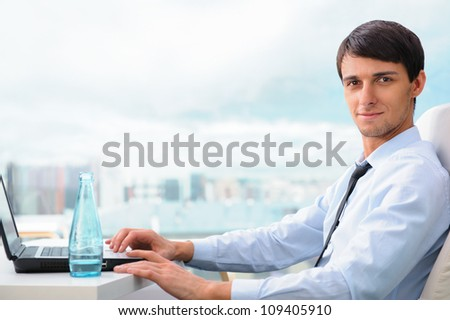 Happy executive sitting in front of laptop and looking at camera - stock photo