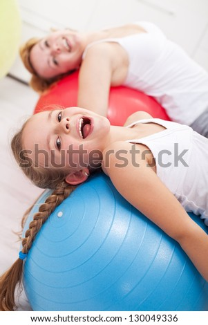 Happy exercising - little girl and her mother doing gymnastic