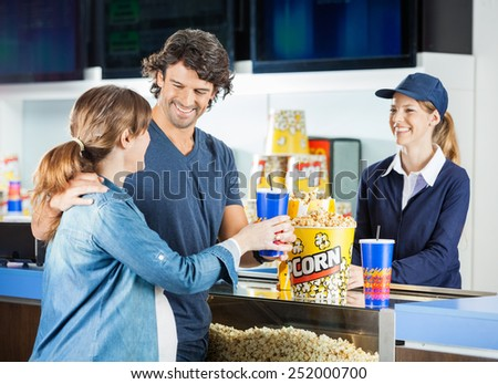 Happy expectant couple buying snacks from female seller at cinema concession stand - stock photo