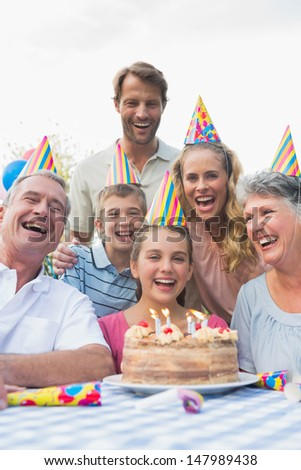 Happy extended family celebrating a birthday laughing at camera outside - stock photo