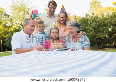 Happy extended family celebrating little girls birthday outside at picnic table - stock photo