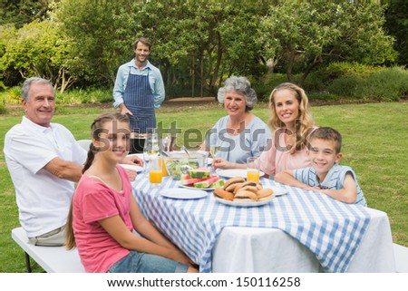 Happy extended family having a barbecue being cooked by father looking at camera - stock photo