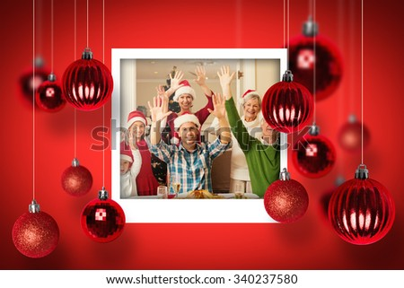 Happy extended family in santa hat cheering at camera against christmas photographs - stock photo