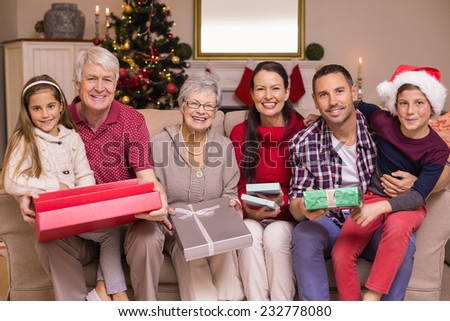 Happy extended family looking at camera at christmas time at home in the living room - stock photo