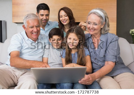 Happy extended family using laptop on sofa in the living room at home - stock photo