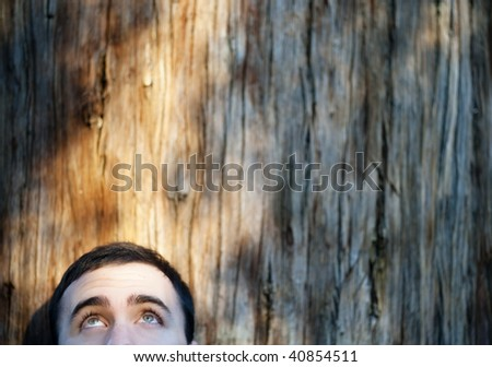 Happy eyes looking at wooden textured copy space. - stock photo