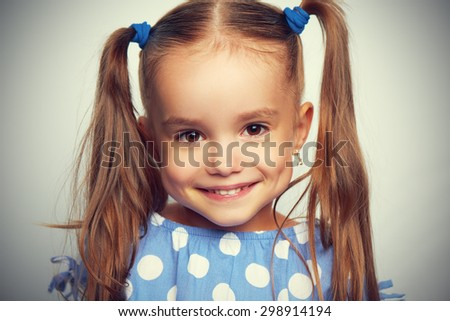happy face funny child girl in a blue dress - stock photo