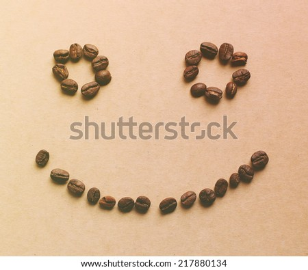 Happy face shaped of coffee beans with retro instagram filter effect - stock photo