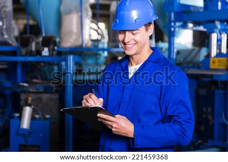 happy factory worker writing report - stock photo