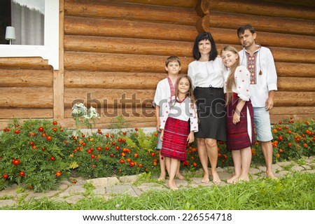 Happy famiily on the background of traditional Ukrainian house. Ukrainian traditional clothes