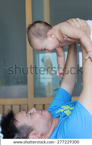Happy family, A baby and father on the bed - stock photo