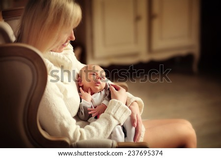 Happy family: a close up portrait of a beautiful young blonde woman in white clothes sitting in a chair and holding her cute newborn baby in a white suit. - stock photo