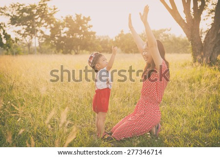 Happy family. A mother and son playing in grass fields outdoors at evening.Vintage Tone and copy space.