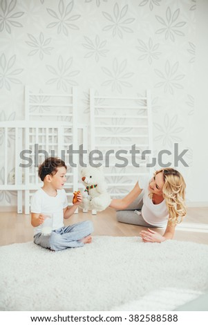happy family.a pregnant woman.interior.milk. Mom plays with son. cheerful women. enjoyment. mather playing, with son - stock photo