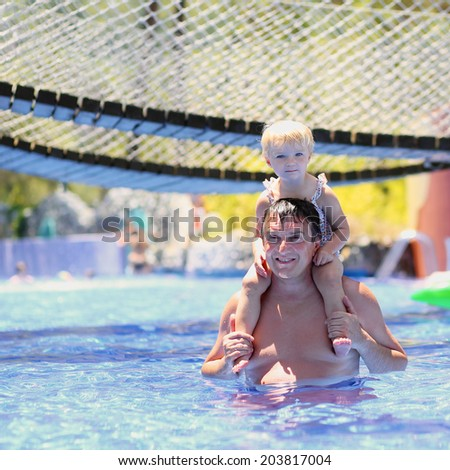 Happy family, active father with little child, adorable toddler girl, having fun together in outdoors swimming pool in aquapark during sunny summer sea vacation in tropical resort - stock photo