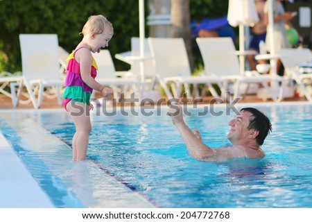Happy family, active father with little child, adorable toddler girl, having fun together in outdoors swimming pool in aquapark during sunny summer sea vacation - stock photo