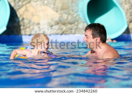 Happy family, active father with little child, adorable toddler girl, having fun together in outdoors swimming pool in water park during sunny summer sea vacations in tropical resort - stock photo