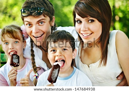 Happy family and group children eat ice cream. Outdoor. - stock photo