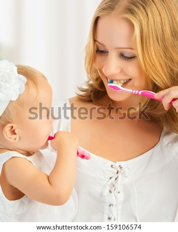 happy family and health. mother and daughter baby girl brushing their teeth together - stock photo