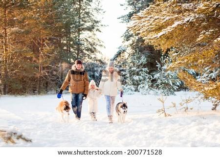 Happy family and husky dog in winter park - stock photo