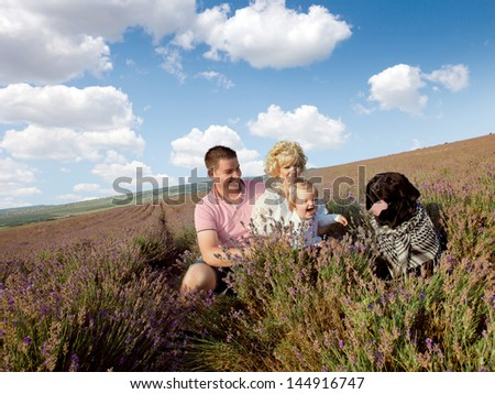 happy family and labrador dog  having fun outdoors in lavender field