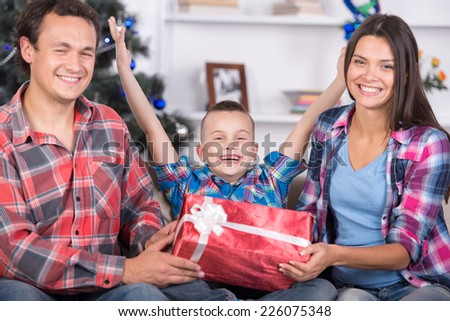 Happy family are giving presents for each other. It's Christmas time. - stock photo