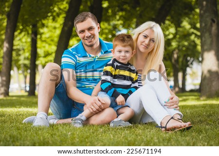 Happy family are plaing in the summer park - stock photo